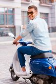 foto of vespa  - Rear view of cheerful young man in glasses riding scooter along the street and looking over shoulder - JPG