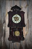 stock photo of pendulum clock  - old pendulum clock on the background of wooden wall - JPG