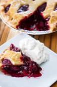 pic of cherry pie  - view form above of a fresh baked cherry pie with a slice on a white plate - JPG