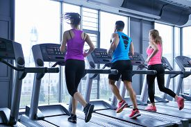 picture of cardio exercise  - group of young people running on treadmills in modern sport  gym - JPG