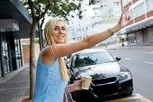 pic of cabs  - young happy girl calling for taxi cab along city sidewalk with coffee cup - JPG