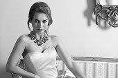 foto of aristocrat  - black and white fashion indoor portrait of pretty brunette girl with aristocratic style sitting on ancient sofa with classic hair-style wearing pink elegant dress and shiny necklace. Smiling and looking in camera