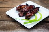 pic of scallion  - Chinese pork ribs with scallions on a white square plate - JPG