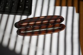 pic of jalousie  - One ball pen in brown wooden case on table with white paper and keyboard and jalousie shade in stripes on office background horizontal picture - JPG