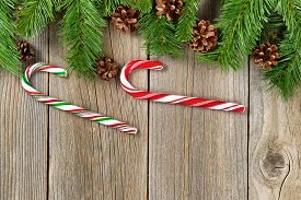 foto of candy cane border  - Christmas border with pine tree branches cones and candy canes on rustic wooden boards - JPG