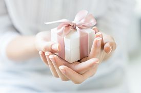pic of hands up  - Close up shot of female hands holding a small gift wrapped with pink ribbon - JPG