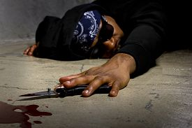 stock photo of gang  - young black male murdered in a street alley with a bloody knife - JPG