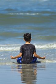 foto of wet  - A young boy all wet is meditating on the beach in the wet sand near Daytona Beach - JPG