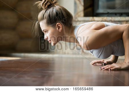poster of Closeup of young happy attractive woman practicing yoga, doing four limbed staff, push ups or press ups exercise, chaturanga dandasana pose, working out, wearing sportswear, bra, indoor, home interior