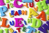 Macro composition of many colorful plastic toy letters and word LEARN