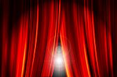 Theatre stage red curtains opening showing a bright light flare behind them