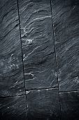 Fraction of a black schist wall with sharp texture