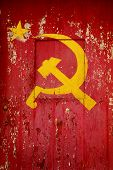 Communist Party symbol in a old wooden door with red paint peeling