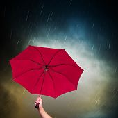 Opened pink umbrella under dark sky with falling rain