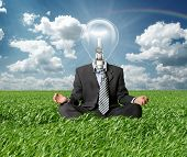 Businessman In Lotus Pose And Lamp-head In Grass