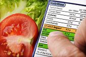 stock photo of differential  - Reading a nutrition label on food packaging with fresh salad background - JPG