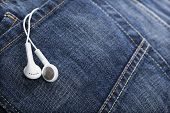 Earbuds on denim jeans with copy space