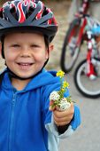 Four year old boy on a cycle trip. Shallow DOF with focus on hand with flowers.