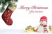 Meia de Natal e boneco de neve com os presentes sobre o fundo branco.