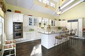 Kitchen with white island and stools
