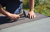 Roofer Installing Asphalt Shingles On House Construction Roof Corner With Hammer And Nails. Roofing  poster