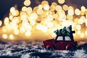 Red car with a Christmas tree driving through snowy road. Fairy lights, wintertime. poster