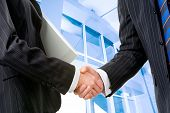 picture of business-partner  - Two partners shaking hands at meeting in front of building - JPG