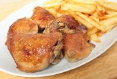 A serving dish piled with roast lemon chicken thighs and French fries, or chips, with a serving spoo