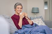 Portrait of smiling senior woman drinking coffee at home while looking at camera. Mature woman sitti poster