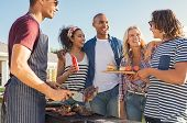 Young multiethnic friends having fun grilling meat enjoying bbq party. Group of happy guys and girls poster