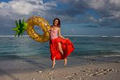 Beautiful Young Woman In Red Long Skirt Hold Ananas Yellow Swimming Ring, Posing On Indian Ocean Bea poster