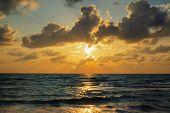 Sunbeam Through Cloud Formation On Ocean Horizon During Sunset. poster