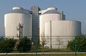 foto of septic  - Silos of an industrial plant in front of a blue sky - JPG