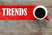 Trends / Cup Of Coffee With Trends Inscription On Wooden Background. poster