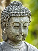 An Aged Statue Of Buddha, In Close-up Portrait Format, Popularly Employed As Garden Ornament Imparts poster