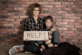 Poor Woman With Her Son Asking For Help Near Brick Wall poster