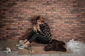 Poor Homeless Woman Eating On Floor Near Brick Wall poster