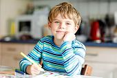 Portrait Of Cute Healthy Happy School Kid Boy At Home Making Homework. Little Child Writing With Col poster