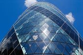 Vertical view of the Gherkin skyscraper with a blue sky background