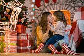 Merry Christmas. Little girl child at home by the fireplace with the family parent mother in red whi poster