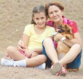 Latin girl with her grandmother and a small pekingese dog at a park