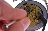 Watchmaker or repair man in action, repairing old watch with tweezers and precision screwdriver