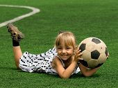 Funny young caucasian girl with soccer ball