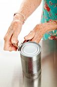 Senior woman's hands with arthritis, struggling to open a can.