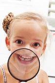 Happy little girl with missing milk tooth showing the gap through magnifier
