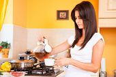 Beautiful young woman making her morning tea in the kitchen