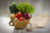 Still life with the clay pot full of vegetables and the breadboard on the tablecloth.