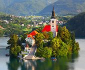 Catholic church situated on an island on Bled lake with mountains and villages on the background