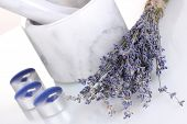 Lavender flowers with mortar and candles isolated on white