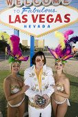 Happy Elvis impersonator with casino dancers in front of a sign
